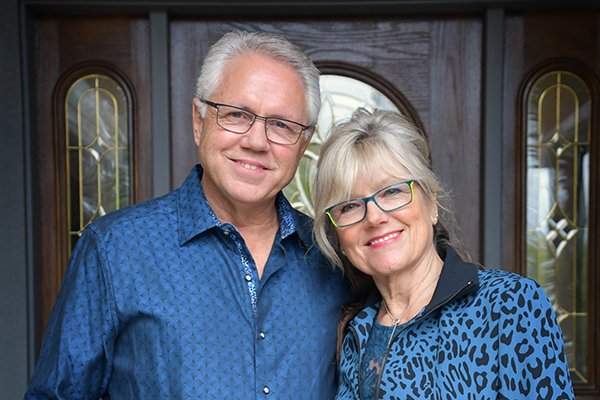 photo of Bill and Joann Truby in blue shirts standing in front of a door - Truby Achievements a leading source for leadership and management training