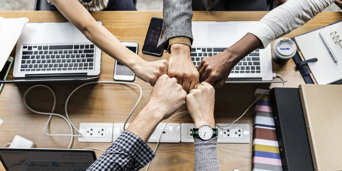 team fist bump while working - from Teamwork Synergy – Get More Done with Less article by Truby Achievements, leading provider of leadership training