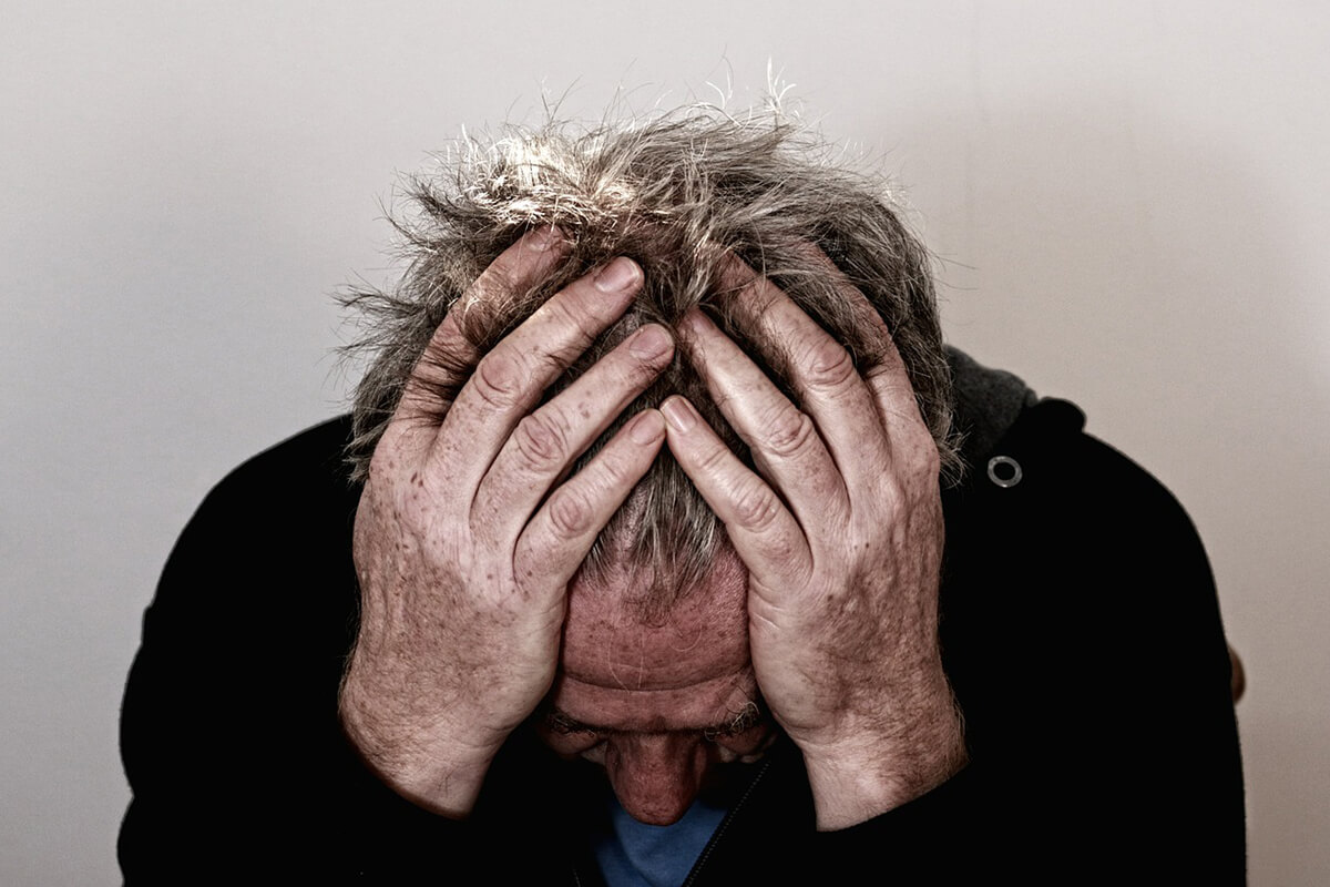 photo of man with head in his hands for free burnout assessment page on truby achievements website