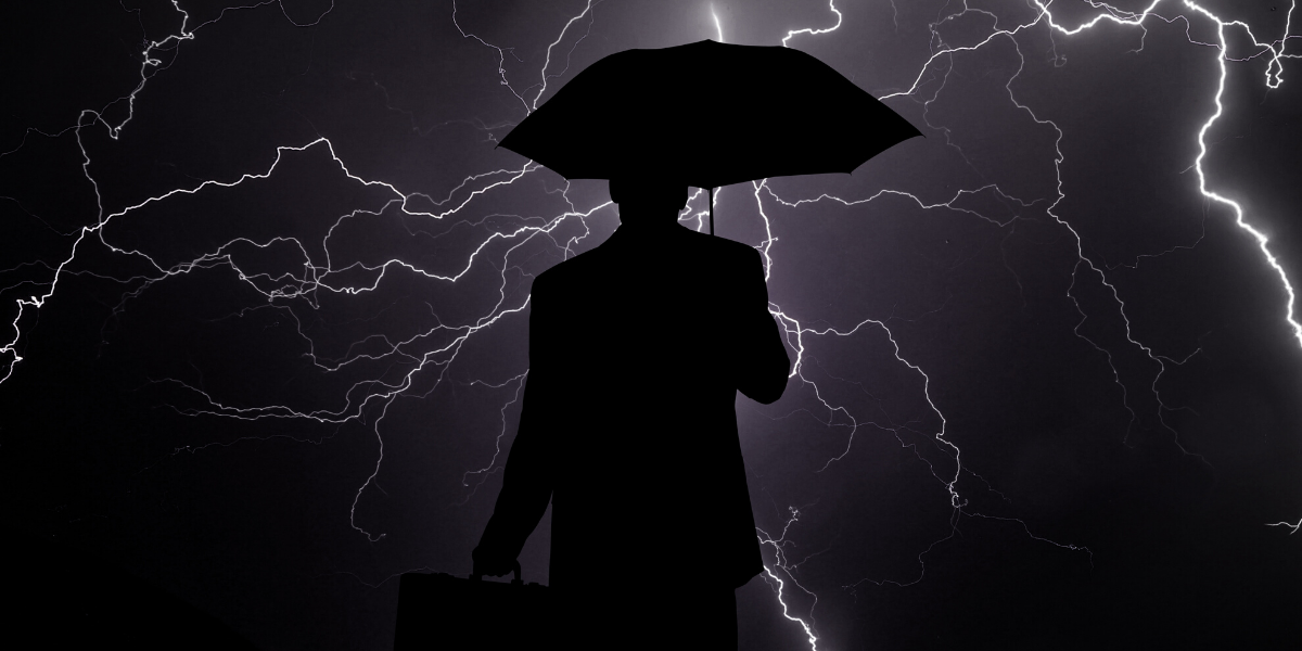 image of a man holding an umbrella in a lightning storm - for Truby Achievements blog post titled 10 tips for how to lead in a crisis