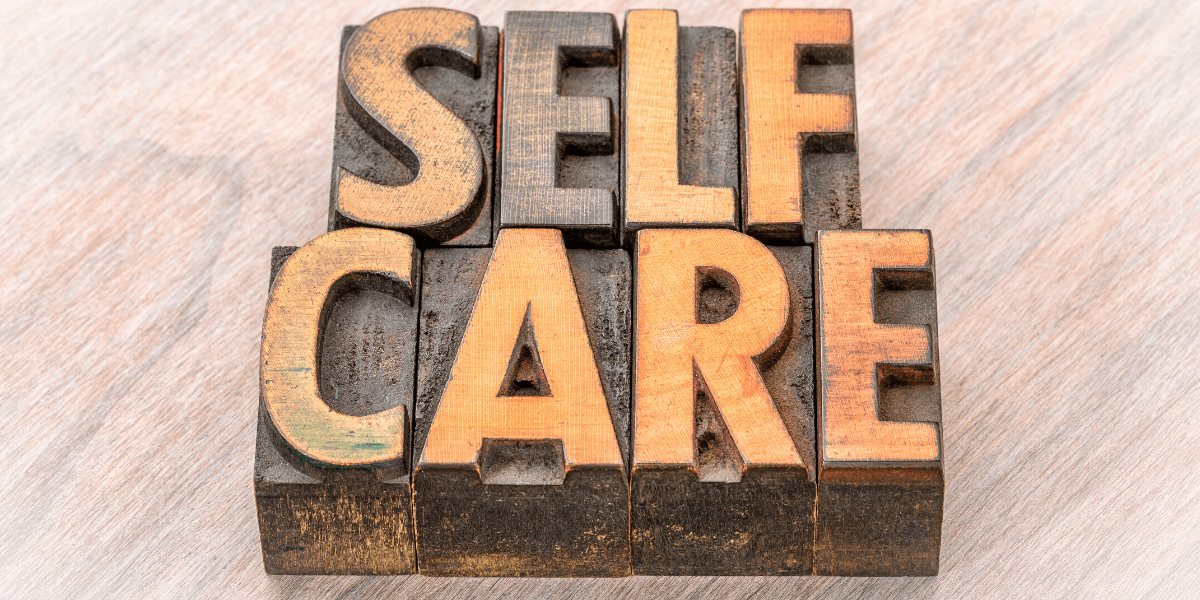 metal stamps saying self care - for Truby Achievements blog post titled quick self-care