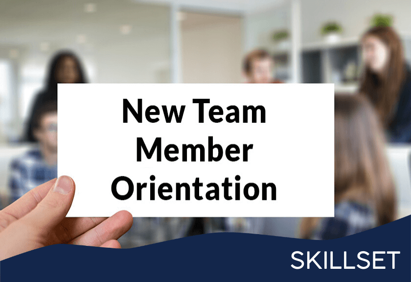 sign in front of a working team that says new team member orientation - featured image for new team member orientation skillset from truby achievements