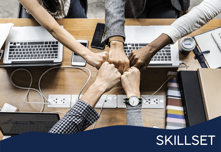 team fist bump over a working table - featured image for teamwork training skillset from truby achievements