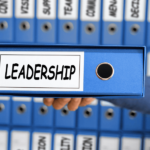 work binders with one held up with words leadership on spine - featured image for Truby Achievements blog post titled 7 key leadership skills
