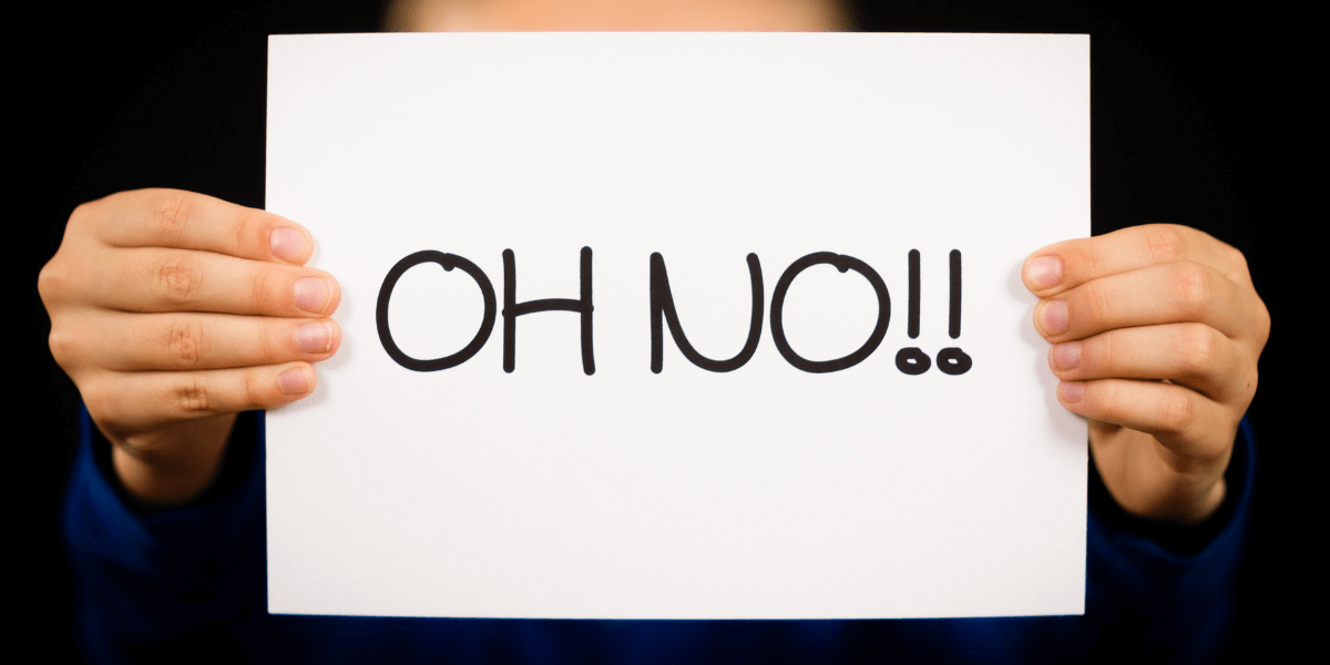 business man holding a sign that says oh no - featured image for Mistakes are Ok - business article from Truby Achievements
